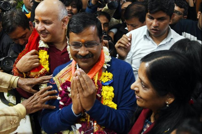 Aam Aadmi Party chief Arvind Kejriwal (C) and his wife Sunita Kejriwal appear at a rally Tuesday after the party won key seats in the territory of Delhi. Photo by EPA-EFE