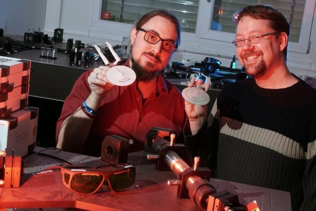 Researchers Alexander Szameit (R) and Marco Ornigotti (L) pose with their laser-based teleportation device and models of the USS Enterprise. Photo by the University of Jena