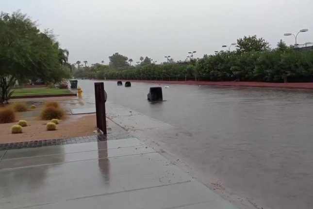 Trash bins float down a flooded Phoenix street. Screenshot: Storyful
