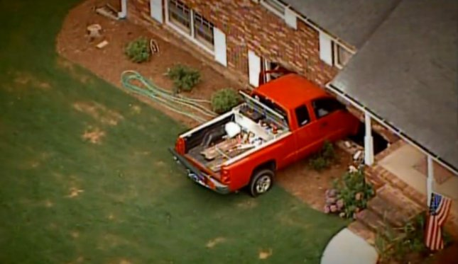 A 2-year-old in Grayson, Georgia drove this red truck into the house of neighbors across the street. (Screenshot via WXIA-TV)