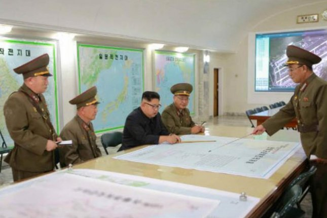 This recent photograph of Kim Jong Un with Pyongyang's strategic command includes an image of Guam on the far right. File Photo by KCTV