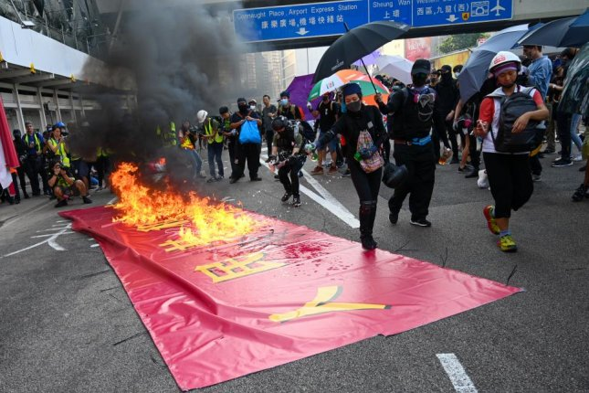 Protesters in Hong Kong burn a banner celebrating the 70th anniversary of the People's Republic of China on Tuesday. Photo by Thomas Maresca/UPI
