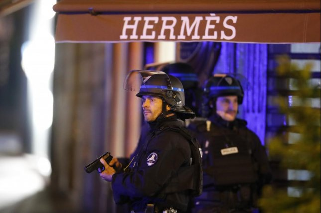 French police officers stand guard after a shooting on the Champs-Elysees in Paris, France, on Thursday killed one police officer, wounded two and left the gunman dead. Photo by Ian Langsdon/EPA