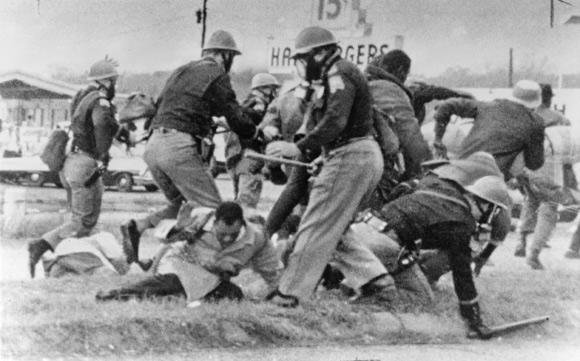 Original Caption: SNCC leader John Lewis (light coat, C) cringes as burly state trooper swings his club at Lewis' head 3/7 during attempted Negro march on the state capitol at Montgomery--Lewis later was admitted to a local hospital with a possible skull fracture. UPI File Photo