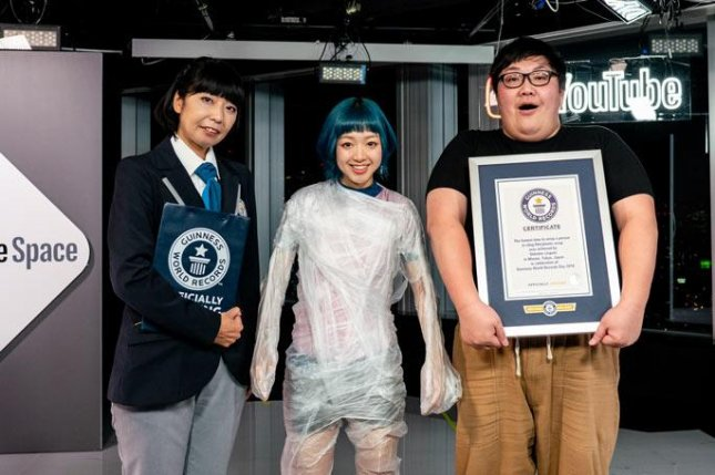 A Japanese YouTuber wrapped a singer from her feet to her shoulders in cling wrap to set a new world record. Photo by Guinness World Records