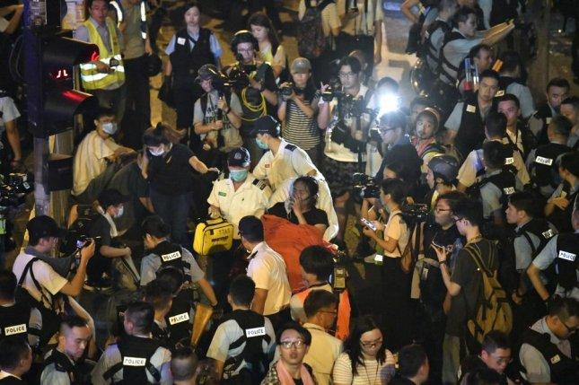 A protester is taken away by medical personnel during clash with police after a rally against amendments to an extradition bill in Hong Kong on Monday. Photo by Edwin Kwok/EPA-EFE