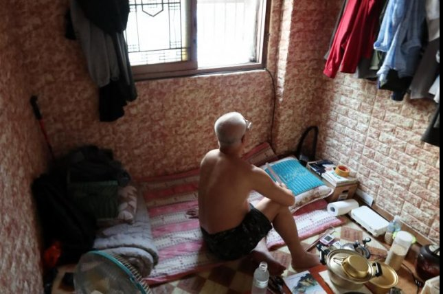 An elderly man uses a handheld fan and an electric fan to cool off at his tiny room that can barely accommodate one person in the southeastern coastal city of Busan on July 19. Photo by Yonhap