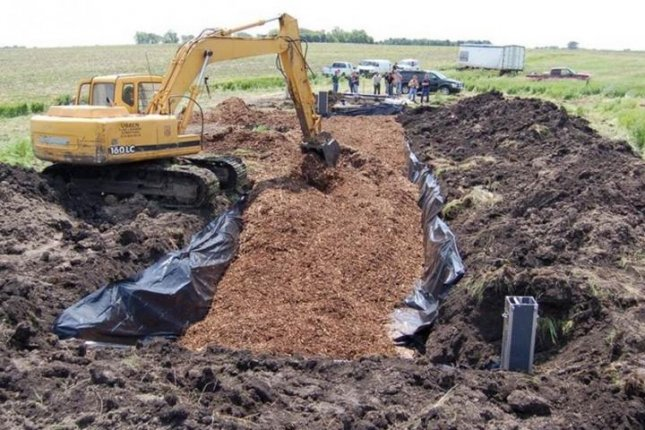A woodchip-filled trench is installed at a soybean farm in Iowa. The so-called bioreactor helps keep nitrogen from running into a nearby stream. Photo by Laura Christianson
