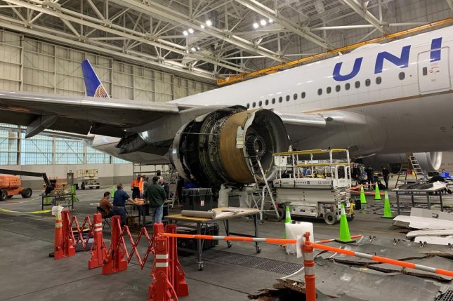 Federal investigators examine a United Airlines Boeing 777 in Denver, Colo., after the plane made an emergency landing on its way to Hawaii due to engine failure. Photo courtesy NTSB/Flickr