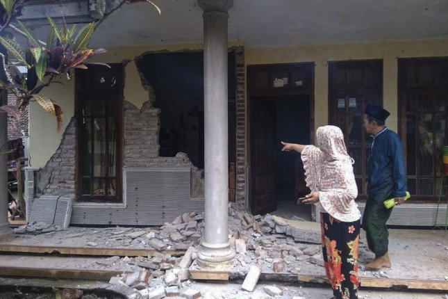 People inspect a damaged house following a 6.0 magnitude earthquake hit in Malang, East Java, Indonesia Saturday. The strong quake struck off Java island killing at least seven people and injured some others, BNPB said. Photo via Indonesia National Board for Disaster Management/EPA-EFE