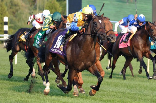 Robert Bruce (yellow silks) wins Saturday's Arlington Million, capping a stellar day for trainer Chad Brown. Photo courtesy of Keely Sorrows/Coady Photography