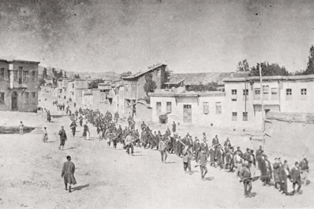 Armenian civilians, escorted by armed Ottoman soldiers, are marched to a nearby prison. Photo by Wikimedia Commons