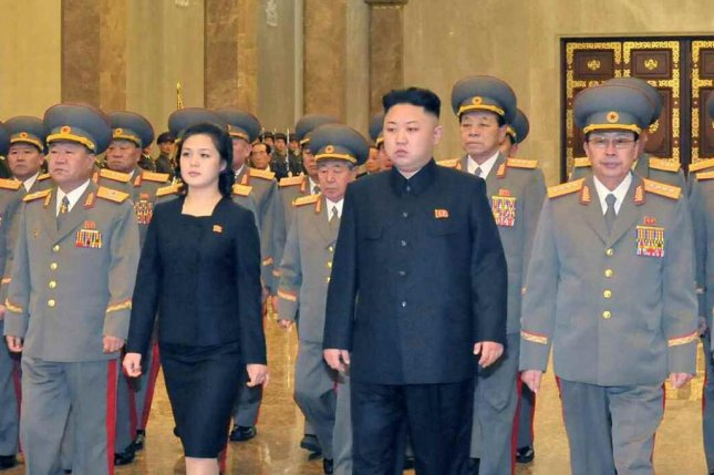 North Korea's Kim Jong Un and wife, Ri Sol Ju, have been photographed in public wearing imported luxury items, but the North Korean leader said import worship is a disease. File Photo by KCNA/Yonhap
