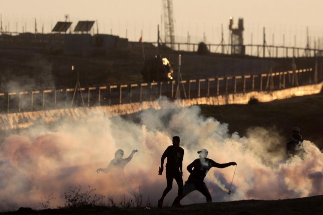 Palestinians hurl Israeli tear gas grenades back at Israeli troops during a clash at the border between Israel and eastern Gaza Strip in December. Finnish lawmaker Anna Kontula was arrested this week for trying to cut through a fence at the border. Photo by Mohammed Saber/EPA-EFE