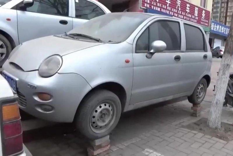 A car parked alongside stairs on a Chinese street balances on bricks. Screenshot: Newsflare
