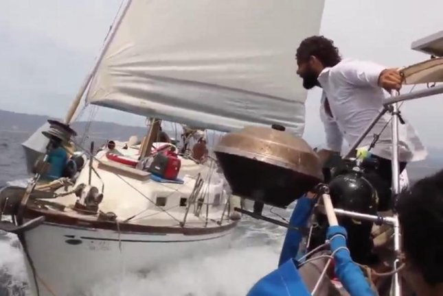 A brave captain prepares to jump between moving sailboats. Screenshot: Storyful