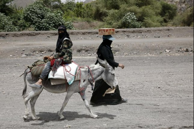 A Yemeni woman leads a donkey transporting her daughter and food aid provided by Mona Relief Yemen in Bani Matar, Yemen on Thursday in the middle of an ongoing civil war. A new United Nations report Friday that a record number of people around the world were displaced in 2020, mostly because of violence. Photo by Yahya Arhab/EPA-EFE