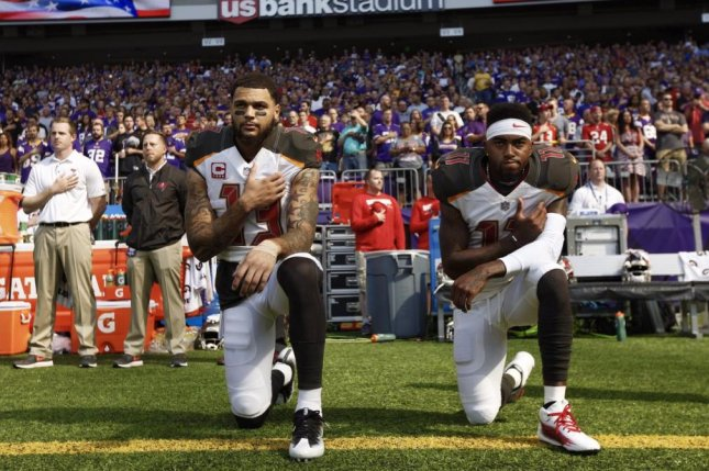 Tampa Bay Buccaneers receivers Mike Evans (left) and DeSean Jackson (right) kneeled with hands on their heart for the National Anthem on Sunday in Minnesota, a few steps behind their teammates who locked arms in unity. Photo courtesy of Loren Elliott/Twitter