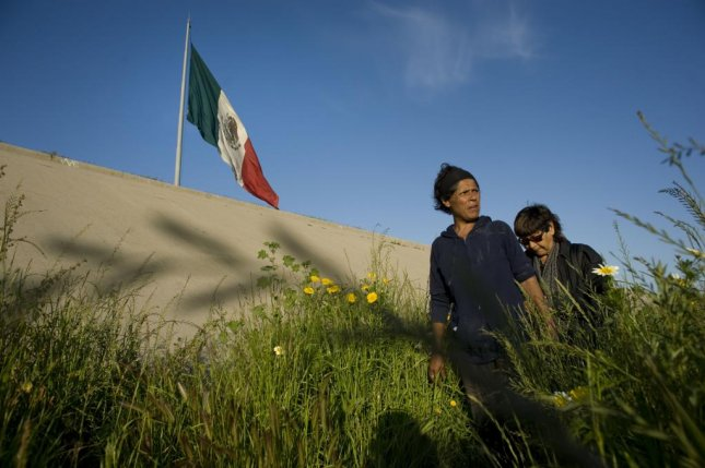 Marta Gomez (L), 42, walks among plants in the Tijuana River canal, which has become home to hundreds of people deported from the United States, in Tijuana, Mexico, in 2013. Migration from Mexico has been declining since 2000. File Photo by David Maung/EPA