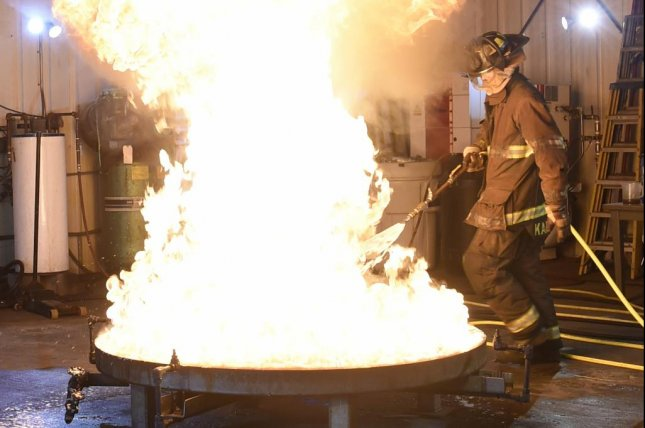 Stan Karwoski, a senior fire test technician at the Naval Research Laboratory, tests the effectiveness of aqueous film-forming foam by spraying it on a gasoline fire in a 28- square foot container in laboratory in Chesapeake Beach, Md., Oct. 25, 2019. Photo byDavid Vergun/DoD