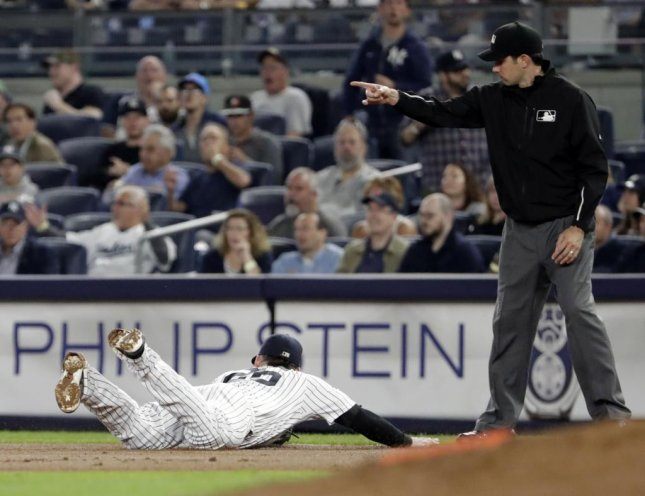 Umpire John Tumpane calls out a baserunner in a recent game. Photo by Jason Szenes/EPA