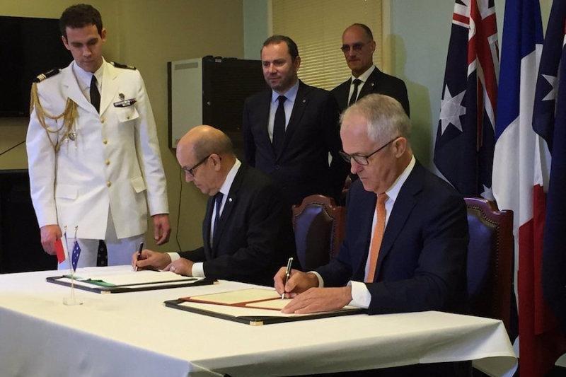 Australian Prime Minister Malcolm Turnbull (R) and French Defense Minister Jean-Yves Le Drian sign an Inter-Governmental Agreement regarding Australia's future submarine fleet. Australian Ministry of Defense photo