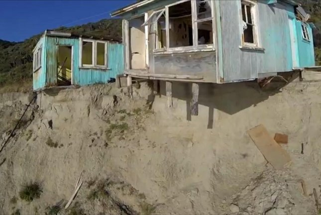 A house in New Zealand is slowly falling from a cliff as the ground beneath it disappears. Screenshot: Newsflare