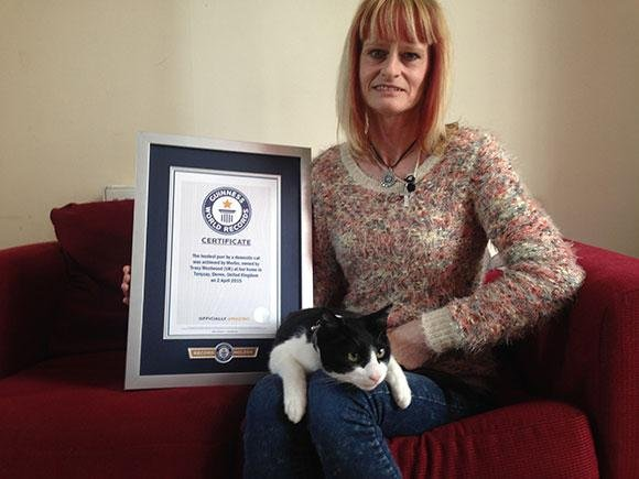Tracy Westwood of Torquay, England, with her cat, Merlin, and a certificate confirming his status as a Guinness World Record holder. Photo courtesy Guinness World Records