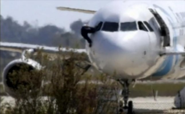An EgyptAir crew member escapes through a cockpit window after a flight from Alexandria to Cairo was hijacked and diverted to an airport in Cyprus on Tuesday morning. Several dozen crew and passengers were aboard. Image courtesy Inform video screenshot