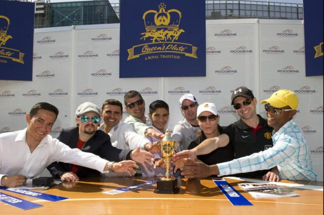 Jockeys riding in Sunday's Queen's Plate at Woodbine grab for the trophy awarded the winner of Canada's most prestigious race. (Woodbine photo)