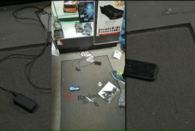 A burglar at a Festus, Mo., comic book store left his cellphone behind when he fled with merchandise including Pokemon cards and KISS action figures. Screenshot: KTVI-TV