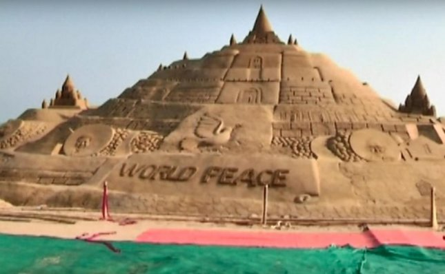 Indian artist Sudarsan Pattnaik constructed the world's largest sandcastle along with 45 students from his Sudarsan Sand Institute. The sandcastle measures 48 feet, 8 inches tall and has a circumference of 530 feet. Screen capture/NTDTV/YouTube
