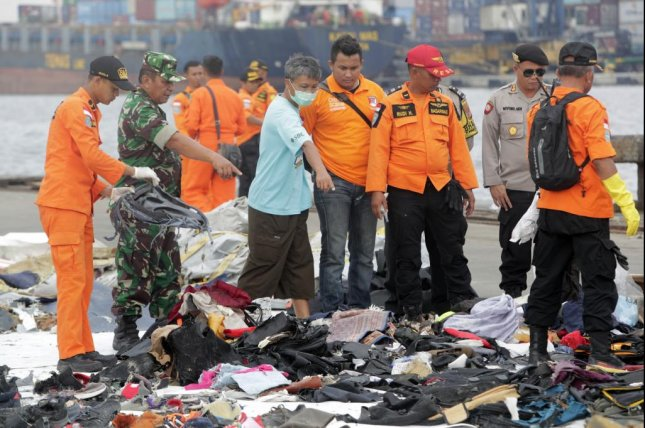 A family member looks for the belongings in wreckage from Lion Air Flight 610, which crashed after leaving Jakarta Monday. Photo by Adi Weda/EPA-EFE
