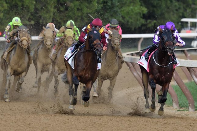 Catholic Boy (red silks) passes pacesetting Mendelssohn (purple) en route to victory in Saturday's Grade I Travers Stakes at Saratoga, the Midsummer Derby. Photo courtesy of Rob Mauhar/NYRA