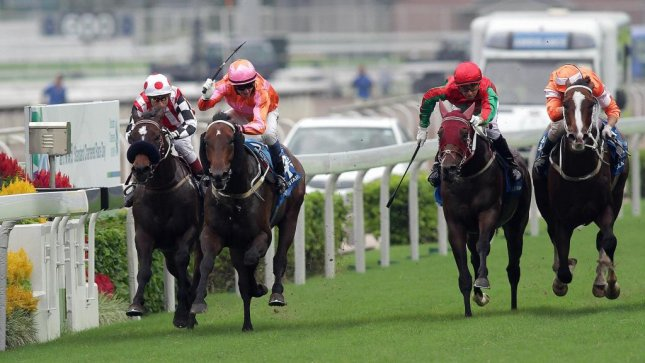 Helene Super Star (No. 4, orange and pink silks) captures the Standard Chartered Champions & Chater Cup at Sha Tin in Hong Kong. (HKJC photo)