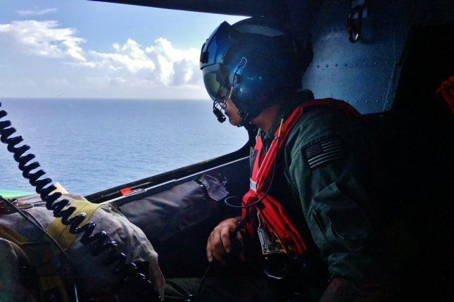 A crewmember aboard a Coast Guard MH-65D Dolphin helicopter looks for survivors of a capsized migrant vessel on July 14, 2016. Friday, a MH-65D Dolphin helicopter was used in the search for two missing pilots whose plane went down off the coast of Hawaii. Officials said the pilots were located and pulled from the Pacific Ocean with only minor injuries. Photo courtesy U.S. Coast Guard