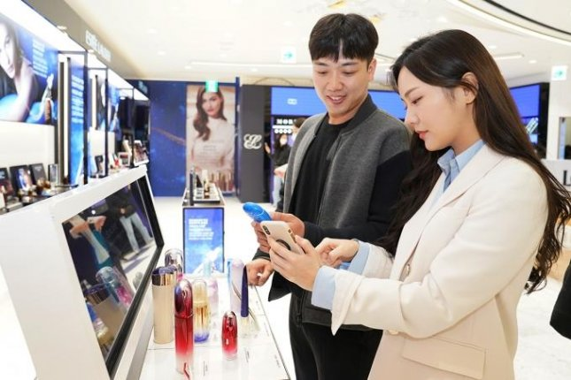 Shoppers check information on products at a Lotte Duty Free in downtown Seoul.  Photo courtesy of Lotte Duty Free