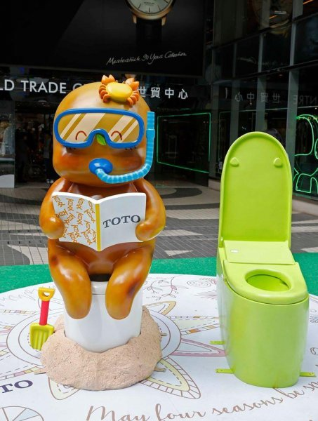 Excreman sits on a smart toilet in an outdoor display in Hong Kong. Photo by TOTO Hong Kong/Facebook