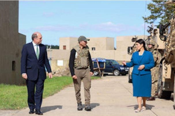 British Defense Secretary Ben Wallace, L, and Home Secretary Priti Patel, C, speak with an unidentified Afghan former interpreter at Wrethasm Camp in Thetford, Britain. Photo courtesy of British Ministry of Defense