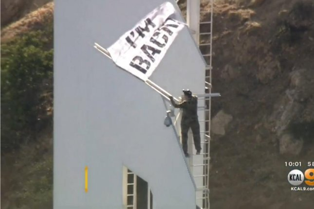 YouTube star Vitaly Zdorovetskiy climbs the D in the Hollywood sign while waving a banner Wednesday. Screenshot: CBS Los Angeles