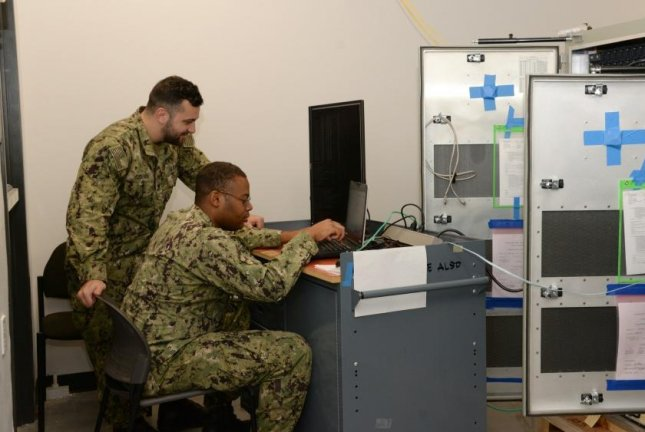 U.S. Navy Information Systems Technicians 2nd Class Hakan Ozdemir, left, and Jchaun Rountree perform operational checks in the Naval Information Warfare Center Pacific's Network Integration and Engineering Facility. Tekla Research was awarded an $83 million contract to work on work on warfare systems for Navy aircraft and aviation systems. Photo by Rick Naystatt/U.S. Navy