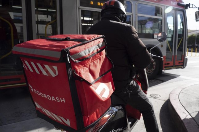 A DoorDash delivery person waits to pick up an order in San Francisco, Calif., on March 17. Shares of the company began trading on the NYSE Wednesday. File Photo by John G. Mabanglo/EPA-EFE