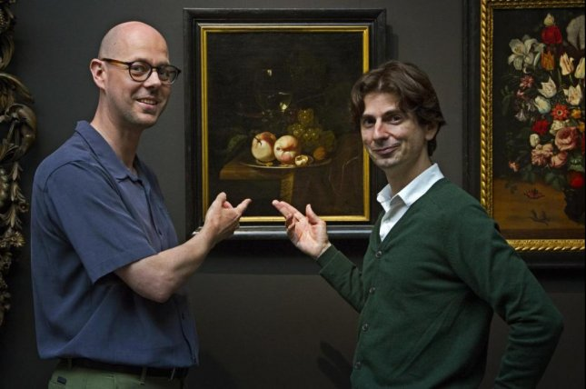 Biologist Ive De Smet and art historian David Vergauwen, co-authors of a study on artistic depictions of evolution of plant-based foods, stand in front of still-life painting of fruits. Photo by Liesbeth Everaert