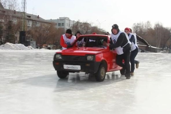 A team pushes their car across the ice in a Russian city in an automobile curling exhibition match. Screenshot: TASS/YouTube