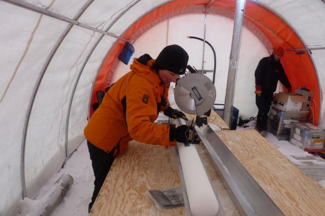 Researcher Liz Thomas is pictured measuring a newly drilled ice core in Antarctica. Photo by British Antarctic Survey