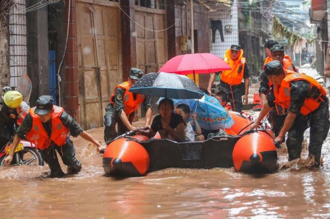 Paramilitary police officers evacuate residents in a flooded residential area in Wanzhou in southwest China's Chongqing Municipality on July 16. The flooding this summer is the most serious disaster since 1998, Chinese authorities said Thursday. File Photo by Zou Mou/EPA-EFE