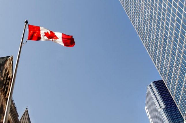 A Canadian flag flies outside of a downtown office building in Toronto, Ontario. File Photo: Oceanfishing / Shutterstock