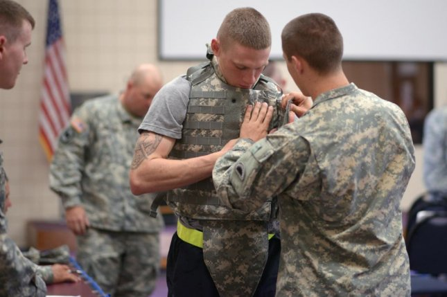 U.S. Army Sgt. Benjamin Herrmann is fitted for body armor with the help of Spc. Ryan Johnson during the Army National Guard's Best Warrior Competition in 2013. U.S. Army National Guard photo by Sgt. Betty Boyce/Released
