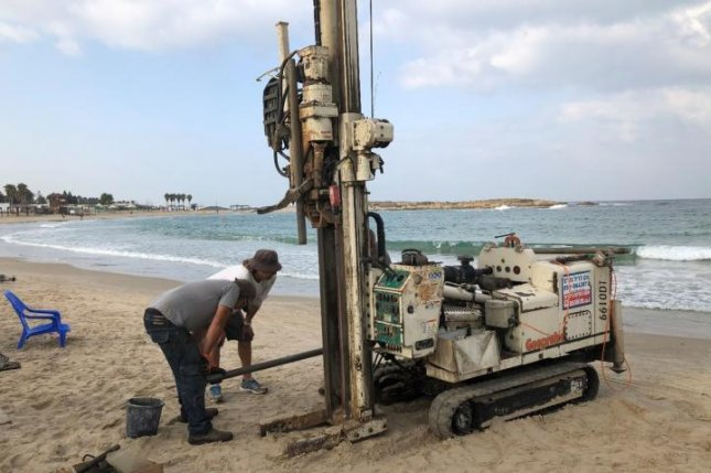 Researchers use a drilling rig to extract a sediment core from the eastern Mediterranean coast, near Tel Dor, Israel. Photo by T. E. Levy