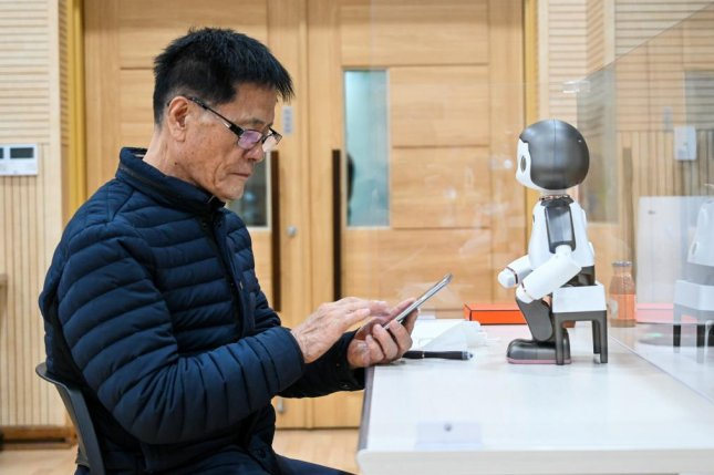 A robot teaches a senior citizen how to use KakaoTalk, a ubiquitous communications app in South Korea. Photo by Thomas Maresca/UPI